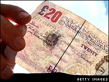 Person taking 20 pound note out of wallet