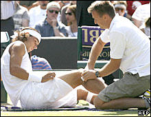 Rafael Nadal receives treatment for a knee injury