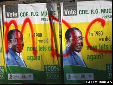 Opposition party graffiti on campaign posters for Robert Mugabe