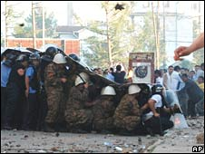 Police shield themselves from protesters in Ulan Bator on 1 July 2008