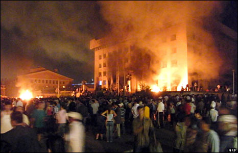 Crowds gather outside the ruling party headquarters as it burns on 1 July 2008