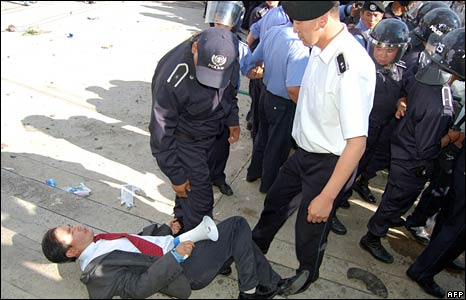 Police pin down a protester in Ulan Bator on 1 July 2008