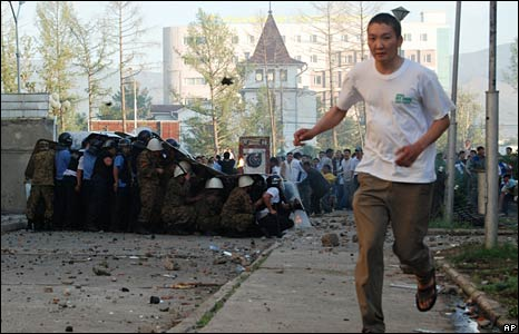 A man runs as police shelter behind shields during clashes in Ulan Bator on 1 July 2008