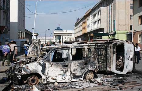 People walk past burnt-out vehicles in Ulan Bator on 2 July 2008
