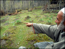 A Kashmiri man points out the unmarked graves in Kichihama village in Kashmir <i>(Photo: Nissar Ahmad)</i>