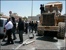 Armed Israeli police and civilians gather around the bulldozer
