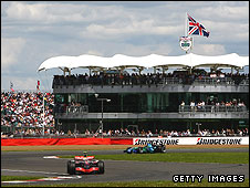 Formula One cars pass by the BRDC headquarters at Silverstone