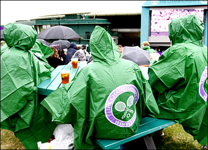 Fans dressed in macs sit on benches watching the big screen at Wimbledon