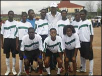 Nigeria's Nwankwo Kanu (with cap on) poses with a team of children