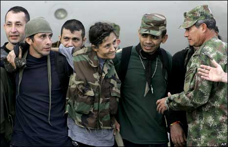 Ingrid Betancourt embraces other freed hostages after arriving at a military base in Bogota
