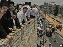 Ultra-Orthodox Jews view scene of bulldozer attack from a rooftop