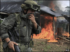 A member of an anti-narcotics squad stands by a burning hut during a raid in Colombia