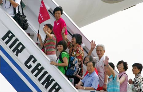 Passengers board a flight to Taiwan at Beijing airport
