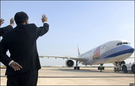 China Airlines officials wave as a flight bound for Shanghai prepares to leave Taoyuan airport in Taiwan