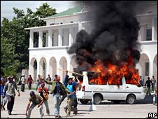 Rioters walk past a burning van in Dili on 28 April 2006