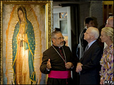 The rector of the Basilica de Guadalupe Diego Monroy (left) explains the icon's significance to Mr McCain and his wife Cindy