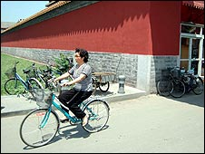 A Chinese woman cycles past a new wall erected to hide shabby housing