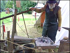 A man uses bellows