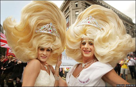 Two men in oversized blonde princess wigs