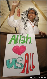 Man with poster reading 'Allah loves us all'