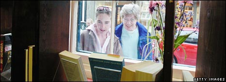 Women peer through the window of a bookshop in Hay on Wye