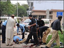 Pakistani policemen help injured colleagues after a suicide attack in Islamabad