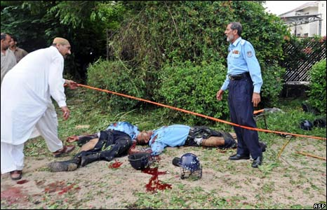 Pakistani policemen gather around the bodies of fallen colleagues at a suicide attack site in Islamabad on 6 July, 2008.