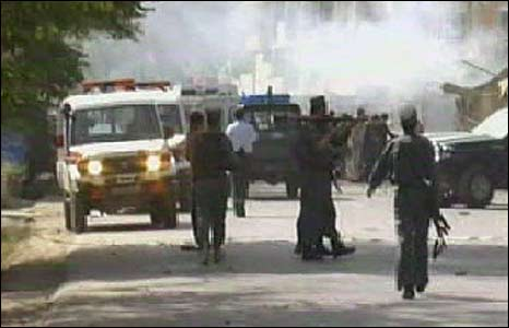 Afghan bystanders and security forces at the scene of a bomb blast in Kabul