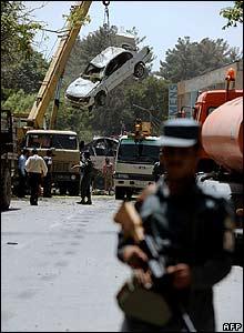 Afghan police stand alert as the wreckage of a car is removed from the scene of the blast
