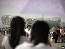 People take their pictures with China's National Stadium, file image