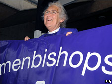 Jean Mayland holds a banner before the debate on bishops