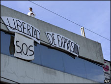 "A banner reading ""Freedom of Expression: SOS"" hangs from the Gamavision building in Quito"