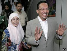 Anwar Ibrahim and his wife Wan Azizah smile after filing a complaint in Kuala Lumpur on 9 July 2008
