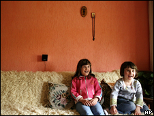 Two children watch television in Pristina, Kosovo
