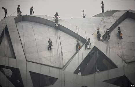 Chinese workers clean the roof of the national stadium in Beijing