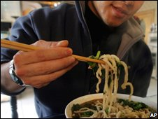 Man enjoys noodles at a restaurant in Beijing