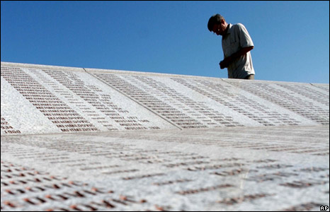 A man walks near a memorial inscribed with the names of some of those killed at Srebrenica