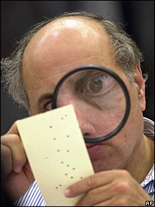 An election worker examines a ballot-paper during the Florida recount in 2000 (File picture)