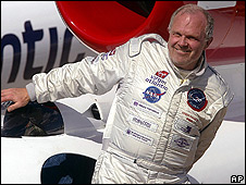 Steve Fossett climbs out of his cockpit after his record-breaking flight around the world in 2005