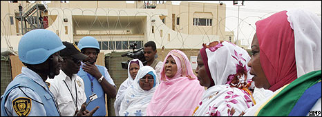 A UN soldier speaks to Sudanese women during a protest against the decision to indict Sudan's president