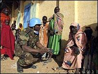 Un integrantes de los Cascos Azules habla con civiles en Darfur