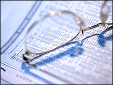 Reading glasses on a financial newspaper