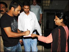 Mahendra Singh Dhoni signs an autograph