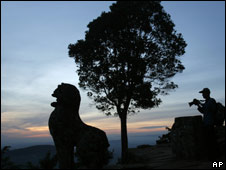 A man takes a photo of a lion on an escarpment at Preah Vihear on 13 July 2008