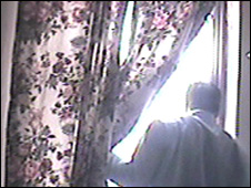 Fauji looks out of curtained window in fauji house