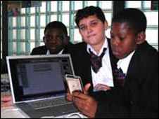 Trevor, 12, Adriano, 12,  and Okeeno, 13, listen back to the report they have recorded on an iPod.