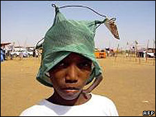 A boy wears a miniature mosquito net on his head to promote malaria awareness