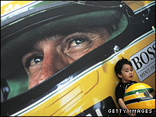 A child poses by a poster of Ayrton Senna