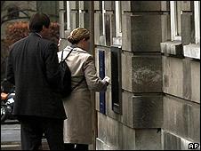 Bank customers queue at ATM
