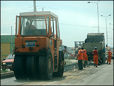 Workers mend a main road in Pristina